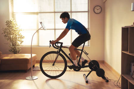 Asian man cyclist. he is exercising in the house.By cycling on the trainer and play online bike games 版權商用圖片 - 156116229