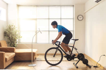 Asian man cyclist. he is exercising in the house and  trainer and play online bike games.He stood up spinning 版權商用圖片 - 156116233