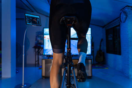 Asian man cycling on the machine trainer he is exercising in the home at night.he play online bike game 版權商用圖片 - 156116243