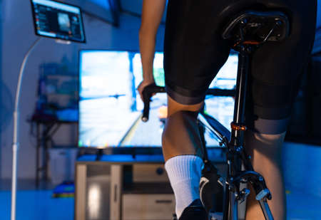 Asian man cycling on the machine trainer he is exercising in the home at night.he play online bike game 版權商用圖片 - 156116249