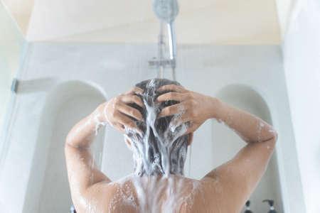 Asian woman washing hair and showering in the bathroom 版權商用圖片