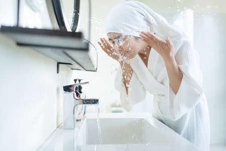 Asian woman washing face in the bathroom 版權商用圖片 - 156019423