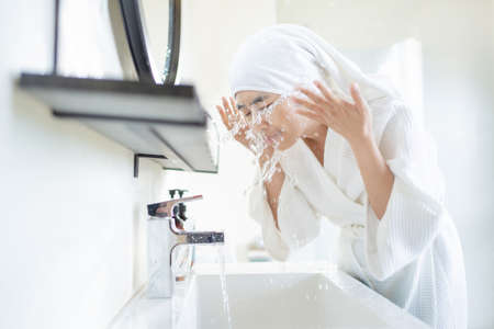 Asian woman washing face in the bathroom