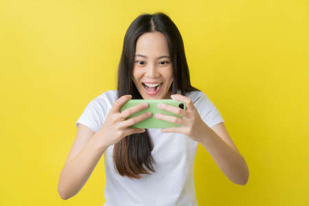 Beautiful Asian woman. She feels shocked with the phone on a yellow background. 版權商用圖片 - 156434090