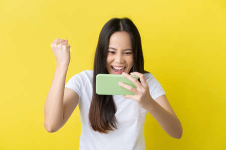 Beautiful Asian woman. She feels shocked with the phone on a yellow background. 版權商用圖片 - 156434533