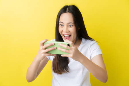 Beautiful Asian woman. She feels shocked with the phone on a yellow background. 版權商用圖片 - 156434072