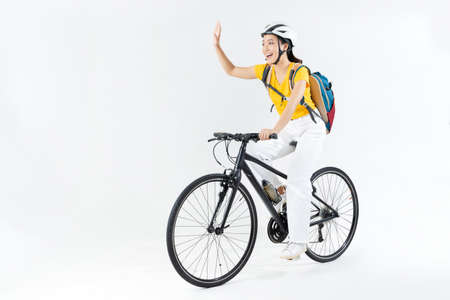 Asian beautiful woman, she is riding a city bike to work.She is greeting.