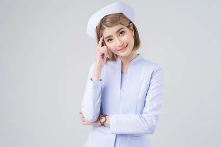 Portrait of a beautiful Asian nurse pointing fingers thinking