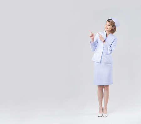 Portrait of a beautiful asian nurse pointing a finger