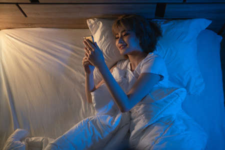 Asian woman using the phone social network at night she is in bed. Banque d'images