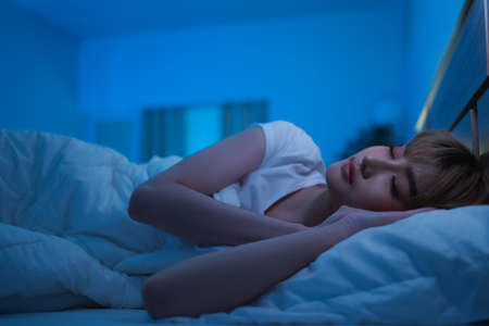 Asian woman sleeping in bed at night