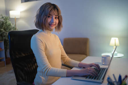 Asian woman Use your computer to play social network at night at her home. Banque d'images