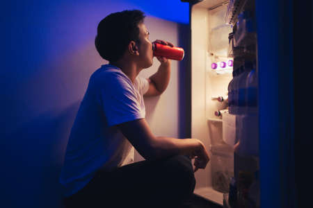 Asian men he is opening the refrigerator.Drink soft drinks at night