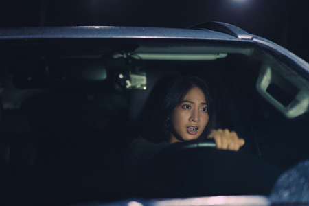 Asian Woman driving alone at night.She was shocked