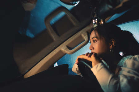 Asian woman is driving alone at night. It's raining. She is lonely. Banque d'images