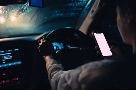 Asian woman is driving alone at night. It's raining. She using smart phone while driving