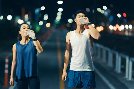 Asian couple, they exercise. They are drinking water