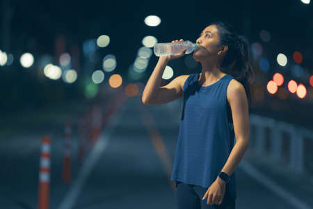 Asian woman exercising and running, she is drinking water.