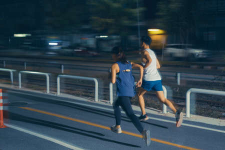 Asian couple jogging in the city streets at night Stock fotó