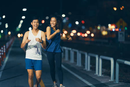 Asian couple jogging in the city streets at night.they are enjoying