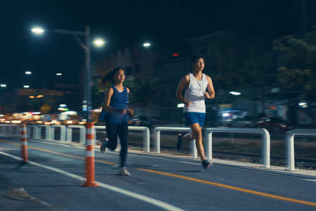 Asian couple jogging in the city streets at night.