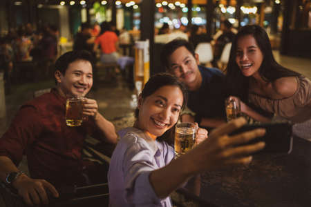 Asian friends Drinking beer outdoors at the brewery for the New Year festival.She is taking a selfie
