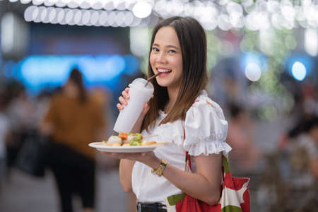 Asian woman tourists eat street food Thailand in the evening