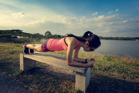 Woman runners are doing planking in the park