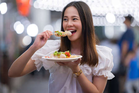 Asian woman tourists eat street food Thailand in the evening Banque d'images