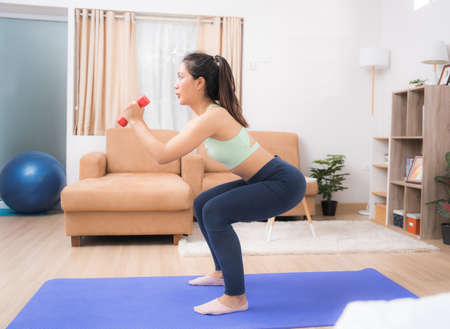 Beautiful Asian woman, she exercises at home, she does squats.