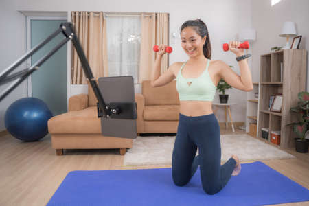 Asian woman exercising at home, she is watching online tutor.