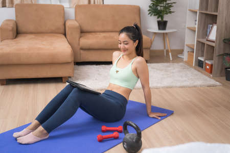 Asian woman Viewing the tablet Home exercise course