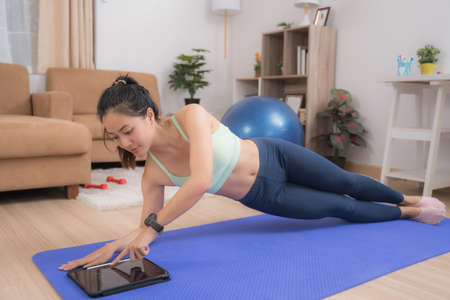 Asian woman exercising at home, she does side plank and stop time.