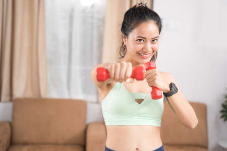 An Asian woman exercising at home, she uses a small dumbbell to practice boxing. 版權商用圖片