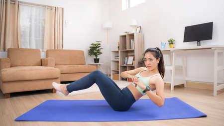 Asian woman exercising at home, she is doing a Russian twist.