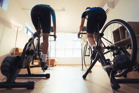 Asian couple. They are exercising in the home.By cycling on the trainer and play online bike games.