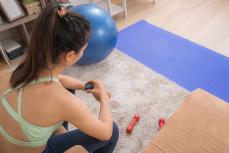 Asian woman using a stopwatch. She exercises at home