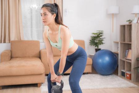 Asian woman exercising at home using pendulum squats 版權商用圖片
