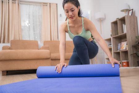 Asian woman picking up a yoga mat, she exercises at home. 版權商用圖片