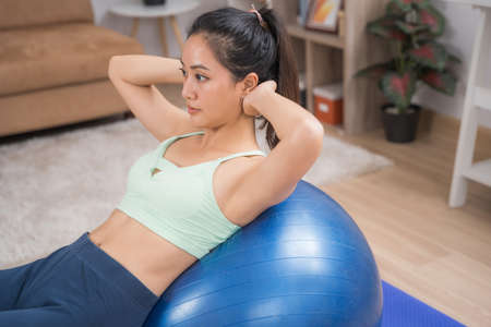 Asian woman exercise at home She's sit-ups on the ball.