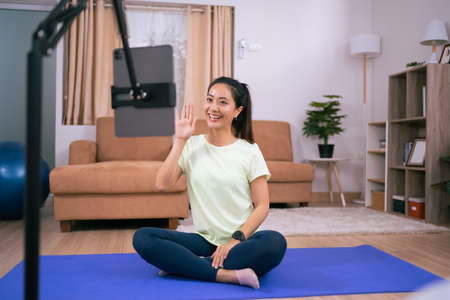 Beautiful Asian woman, she exercises at home, she is broadcasting live exercise