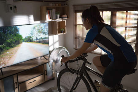 Asian woman cyclist. She is exercising at home. She is playing games in the virtual world.