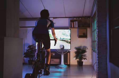 Asian woman cyclist. She is exercising at home. At night she is playing games in the virtual world.