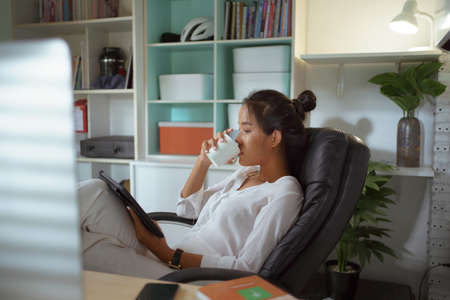 Asian woman is drinking coffee while working