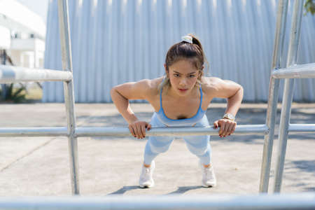 Asian woman Healthy She exercises outdoors. She is doing push ups