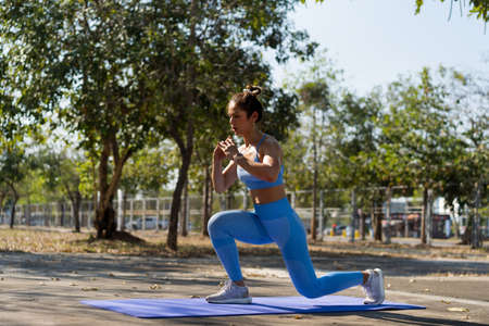 Asian woman Healthy She exercises outdoors, she does leg lunge poses. 版權商用圖片