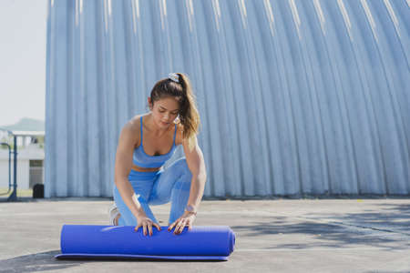 Asian woman Healthy She exercises outdoors. She is folding the mat 版權商用圖片