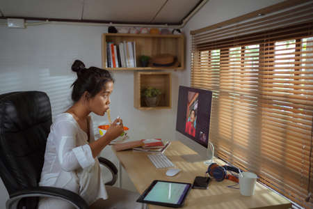 Asian woman eating instant noodles and video calling with the team.