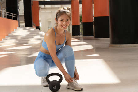 Asian woman Tying shoes ,She is smiling