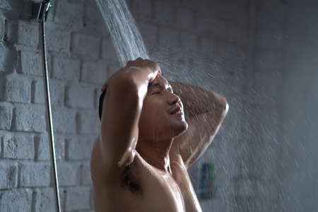 Handsome asian guy Taking a shower in the bathroom 版權商用圖片